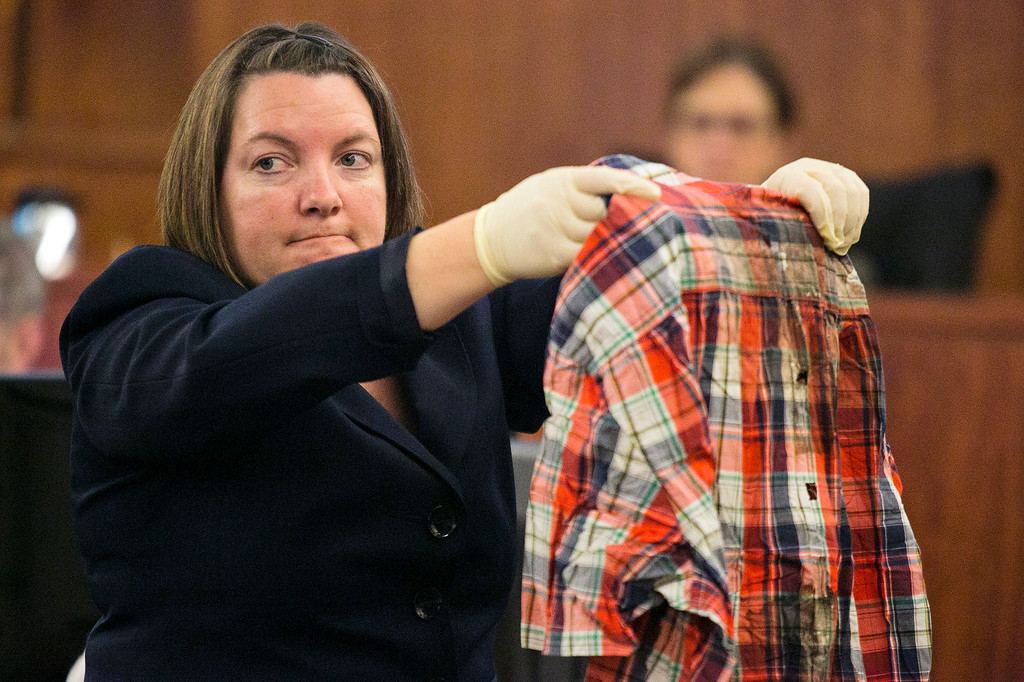 . Massachusetts State Police chemist Sherri Melendez holds up a shirt recovered from the body of Odin Lloyd as she testifies during former New England Patriots NFL football player Aaron Hernandez\'s murder trial at Bristol County Superior Court, Wednesday, March 4, 2015, in Fall River, Mass. Hernandez is accused of the June 2013 killing of Odin Lloyd. (AP Photo/Dominick Reuter, Pool)