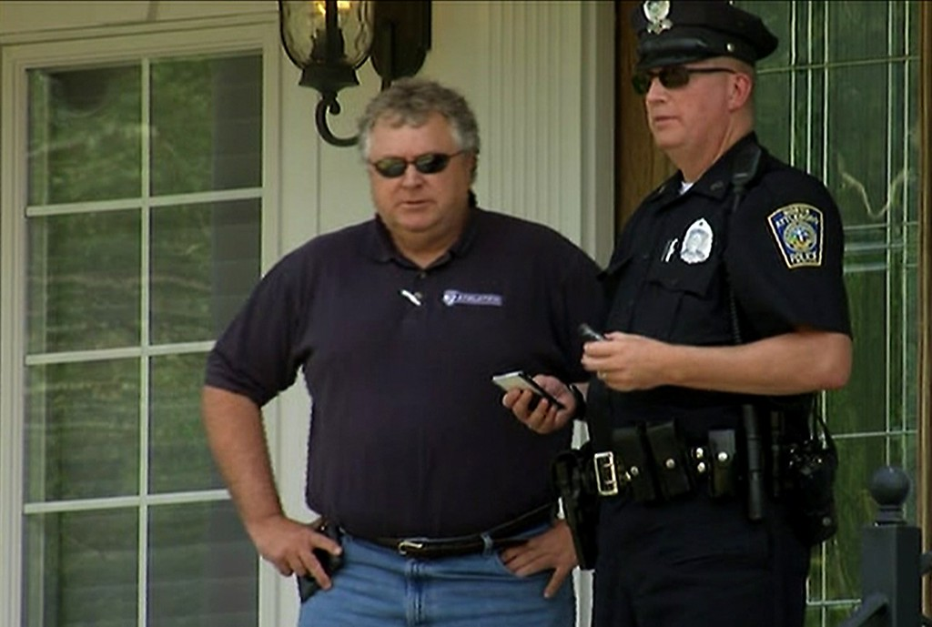 . In this image taken from video, police officers talk outside of  the home of New England Patriots football player Aaron Hernandez, Saturday, June 22, 2013, in North Attleboro, Mass. State police officers and dogs searched Hernandez\'s home as they investigate the killing of Odin Lloyd, a semi-pro football player whose body was found nearby. (AP Photo/ESPN)