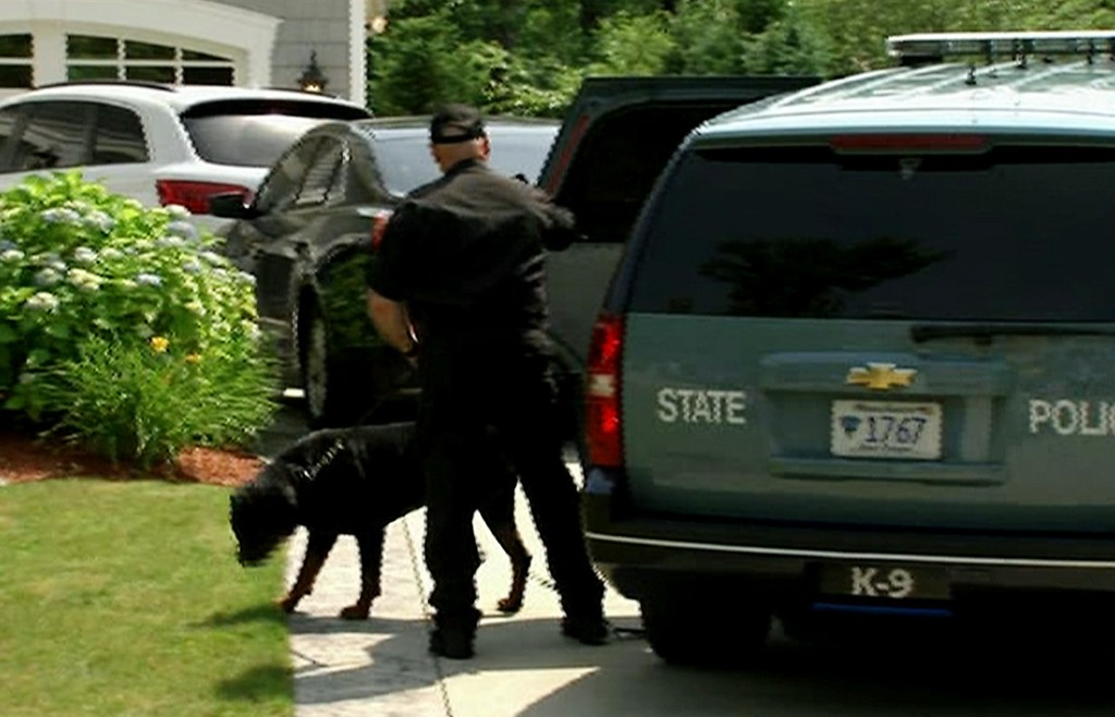 . In this image taken from video, a state police officer and dog arrive outside the home of New England Patriots football player Aaron Hernandez, Saturday, June 22, 2013, in North Attleboro, Mass. State police searched Hernandez\'s home as they investigate the killing of Odin Lloyd, a semi-pro football player whose body was found nearby. (AP Photo/ESPN)