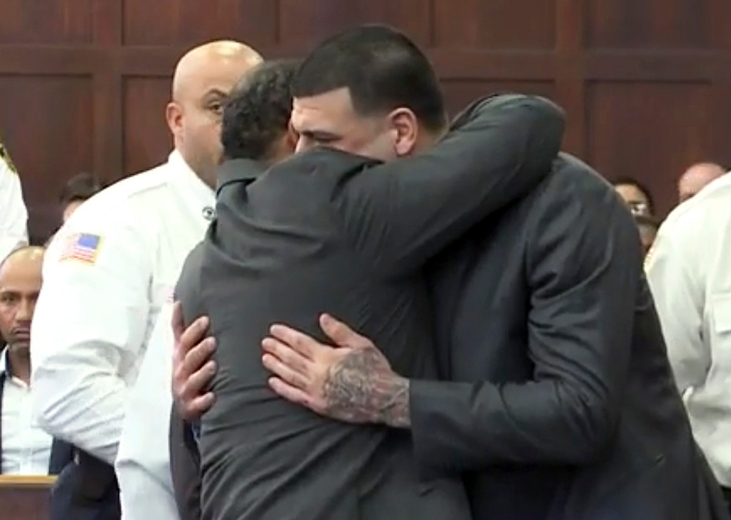 . In this still image from video, Aaron Hernandez, center, is hugged by defense attorney Ronald Sullivan, Friday, April 14, 2017, in court in Boston, after being found not guilty of murder in the 2012 shootings of two men in a drive-by shooting in Boston. (WHDH-TV via AP, Pool)