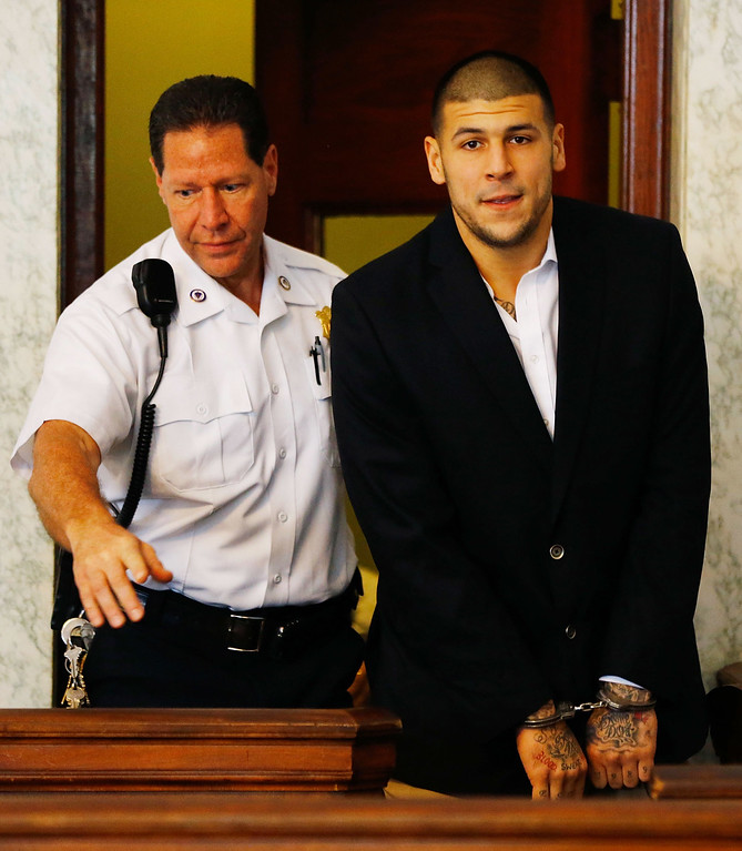 . Aaron Hernandez is escorted into the courtroom of the Attleboro District Court for his hearing on August 22, 2013 in North Attleboro, Massachusetts. Former New England Patriot Aaron Hernandez has been indicted on a first-degree murder charge for the death of Odin Lloyd. (Photo by Jared Wickerham/Getty Images)