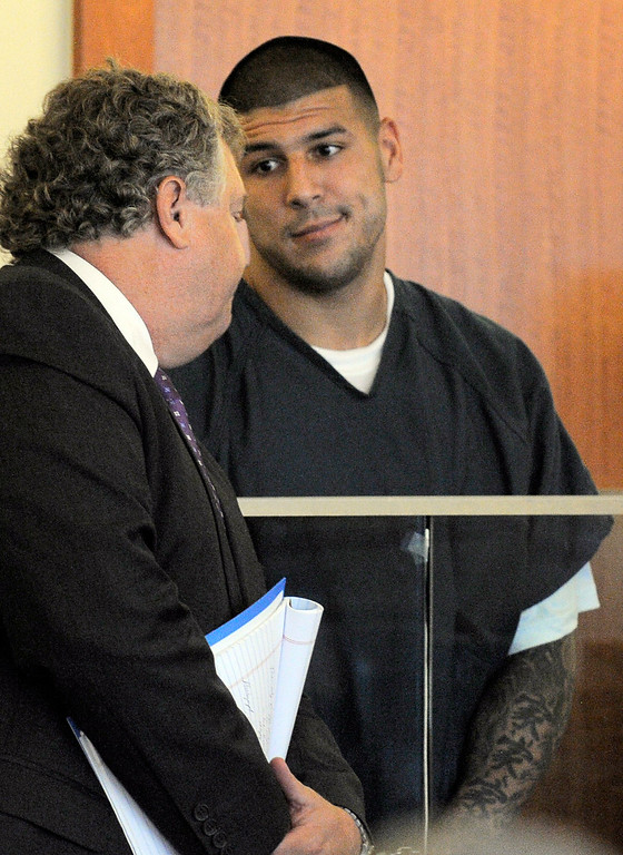 . Former New England Patriots football player Aaron Hernandez, right, reacts to his attorney Michael Fee during a bail hearing in Fall River Superior Court Thursday, June 27, 2013, in Fall River, Mass. Hernandez, charged with murdering Odin Lloyd, a 27-year-old semi-pro football player, was denied bail. (AP Photo/Boston Herald, Ted Fitzgerald, Pool)