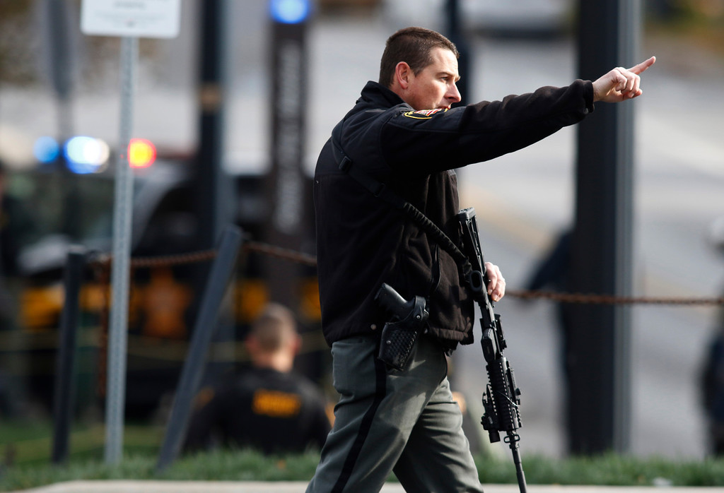 . A law enforcement official motions for people to leave the area outside of a parking garage on the campus of Ohio State University as they respond to an active attack in Columbus, Ohio, on November 28, 2016. Eight people were injured when an attacker apparently drove into a crowd at Ohio State University on Monday, triggering an hours-long lockdown before authorities declared the campus secure. Law enforcement shot and killed one suspect, according to local television station WBNS, which reported that police led two people out in handcuffs from a garage they had surrounded on the university\'s main campus in Columbus.    (PAUL VERNON/AFP/Getty Images)