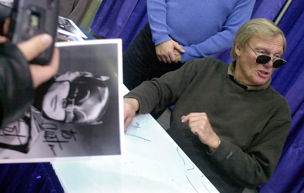 . FILE - In this Feb. 23, 2002 file photo, a fan holds a signed photograph of actor Adam West, right, during the 50th Autorama in Detroit. On Saturday, June 10, 2017, his family said the actor, who portrayed Batman in a 1960s TV series, has died at age 88. (AP Photo/Paul Warner, File)