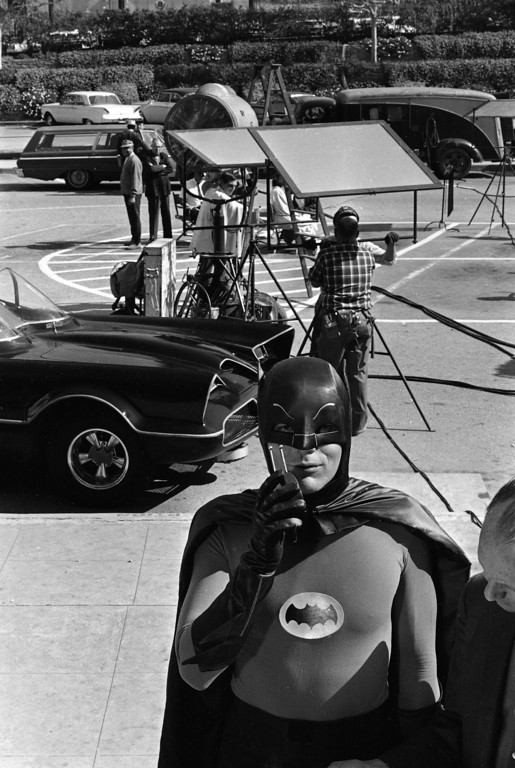 """. File - Adam West, star of the television series """"Batman,"""" stands beside the Batmobile and shows off his """"Bat Radio,"""" on the Hollywood set for the series during filming of an episode, March 18, 1966.  On Saturday, June 10, 2017, his family said the actor, who portrayed Batman in a 1960s TV series, has died at age 88. (AP Photo)"""