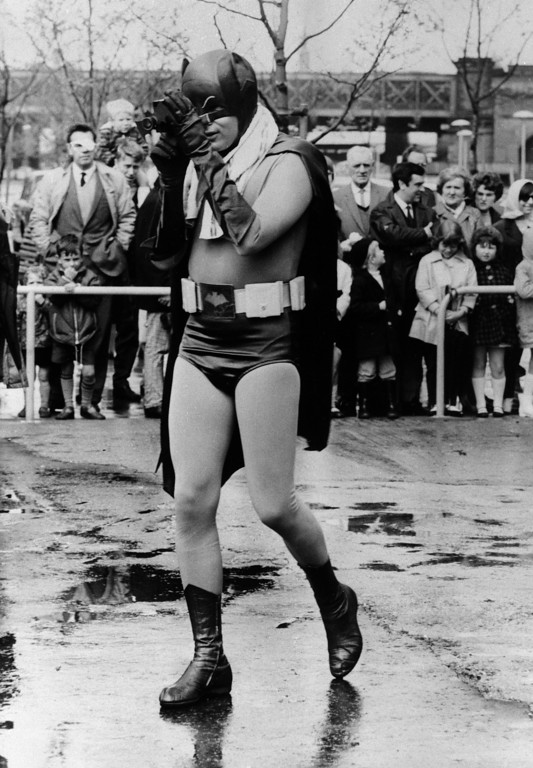 """. Actor Adam West, seen in his """"Batman"""" costume, uses a """"Bat camera"""" in a scene for a commercial film short on road safety being shot in London, May 12, 1967.  (AP Photo)"""