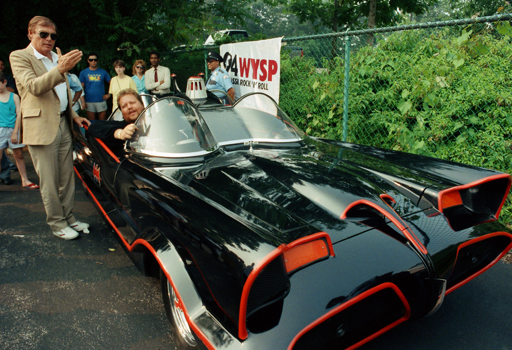 . FILE - In this June 27, 1989 file photo, Adam West, left, stands beside the old Batmobile driven by owner Scott Chinery in Philadelphia. On Saturday, June 10, 2017, his family said the actor, who portrayed Batman in a 1960s TV series, has died at age 88. (AP Photo/Cristy Rickard, File)