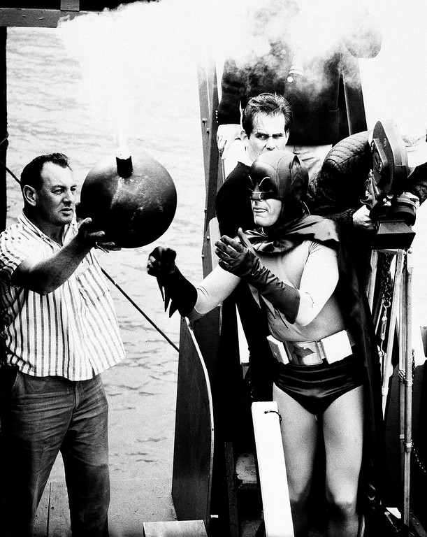 """. Actor  Adam West, playing the Caped Crusader, Batman, waits with anticipation as a prop man is about to hand him a lighted bomb for a scene in the 1966 full length feature, \""""Batman.\""""      In the film Mr. West is handed the bomb with no place to ditch it safely.    (AP Photo)"""