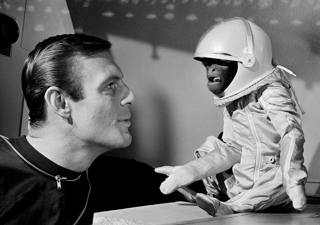 """. File - His own space suit, with oxygen tank, doesn\'t make Barney the monkey any happier as he and actor Adam West view the situation in their space capsule in Hollywood on January 24, 1964.   Barney, a South American woolly monkey, is blasted into space with West, as an astronaut, in the movie, \""""Robinson Crusoe On Mars.\""""   On Saturday, June 10, 2017, his family said the actor, who portrayed Batman in a 1960s TV series, has died at age 88.  (AP Photo)"""