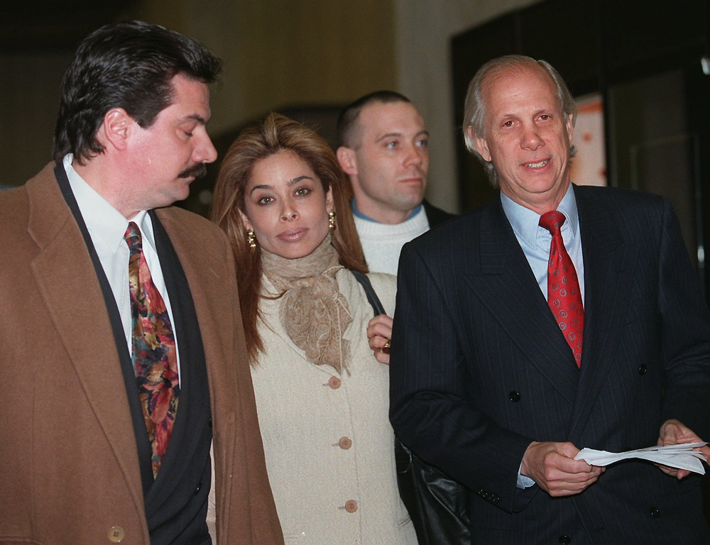 . Faye Resnick, center, is escorted  by her attorney Leonard Marks, right, and Michael Brewer in New York, Monday Feb. 12, 1996.  She completed three days of questioning in the civil lawsuit against O.J. Simpson with detailed descriptions of beatings Nicole Brown Simpson allegedly suffered at the hands of her ex-husband. (AP Photo/Monika Graff)