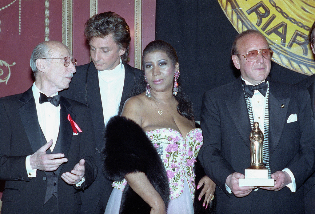 . Clive Davis, head of Arista Records, holds an award presented to him for his contribution to the record industry at the annual Friars Club dinner held at New York\'s Waldorf-Astoria on June 6, 1992.  Standing with Davis are, from left, lyricist Sammy Cahn and singers Barry Manilow and Aretha Franklin.  (AP Photo/Andrew Savulich)