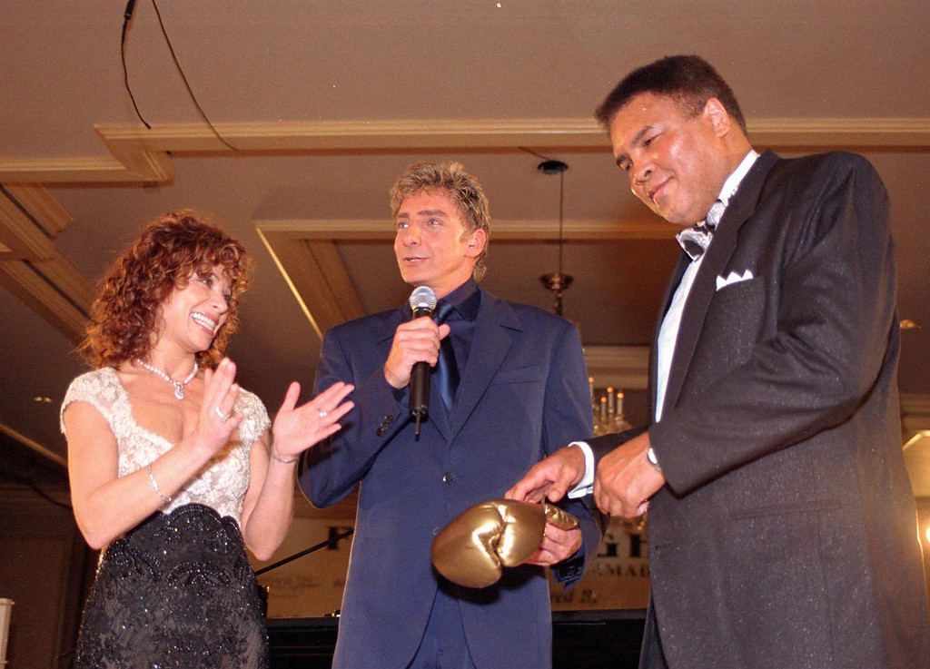 . Muhammad Ali, right, and singer Paula Abdul, left, present Barry Manilow with an autographed boxing glove for his help at the fourth annual Fight Night fund-raiser to benefit the Muhammad Ali Parkinson Research Center Saturday, March 14, 1998 in Phoenix. (AP Photo/Scott Troyanos)