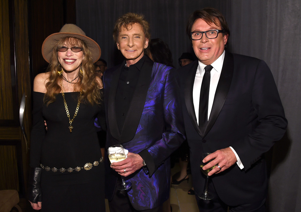 ". File - (L-R) Singer-songwriters Carly Simon and Barry Manilow, and Garry Kief attend the 2016 Pre-GRAMMY Gala and Salute to Industry Icons honoring Irving Azoff at The Beverly Hilton Hotel on February 14, 2016 in Beverly Hills, California.  Manilow tells People magazine that he hid being gay for decades because he thought he would be ""disappointing fans if they knew.\"" The 73-year-old music legend married his longtime manager, Kief, in a 2014 ceremony at their home in Palm Springs, California. (Photo by Larry Busacca/Getty Images for NARAS)"