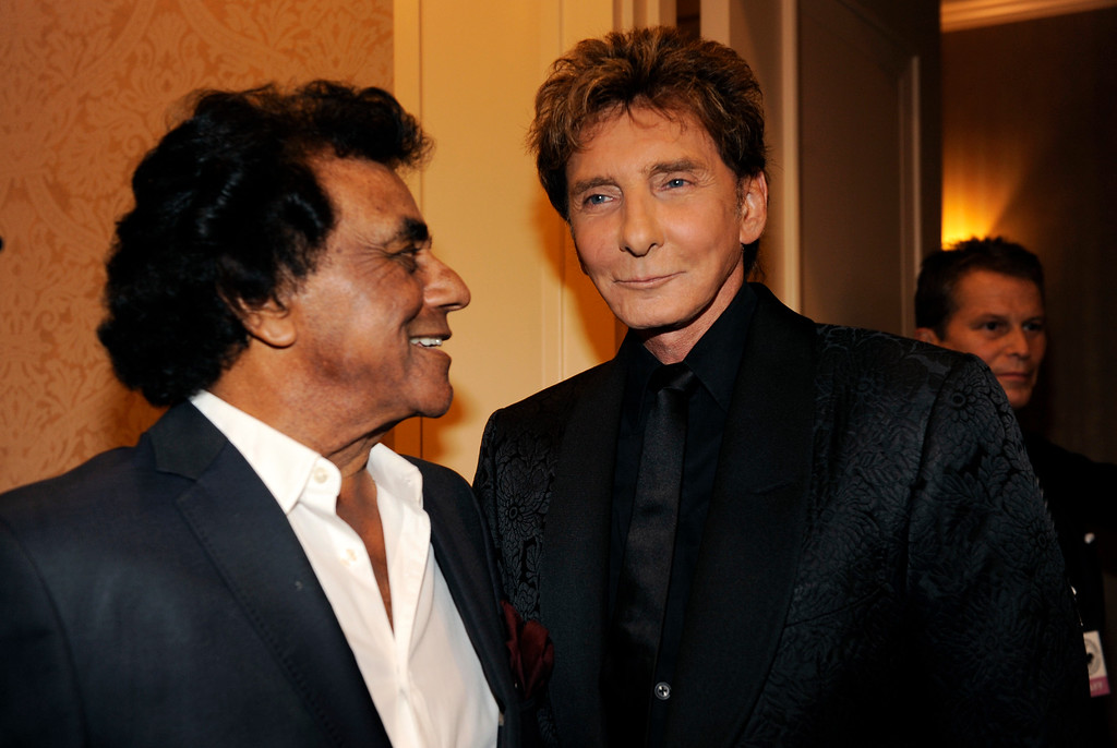 . Singers Johnny Mathis, left, and Barry Manilow mingle at the 2014 Carousel of Hope Ball at the Beverly Hilton Hotel on Saturday, Oct. 11, 2014, in Beverly Hills, Calif. (Photo by Chris Pizzello/Invision/AP)