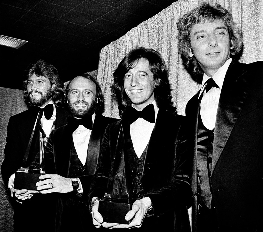 ". Members of the Bee Gees pose with Barry Manilow, far right, at the American Music Awards in Los Angeles, Ca., Friday, Jan. 13, 1979.  The brothers Gibb, from left, Barry, Maurice, and Robin, won awards for favorite popular group and favorite soul album for ""Saturday Night Fever.\""  Manilow won the award for favorite male vocalist in the popular music category, for the second straight year.  (AP Photo/Nick Ut)"