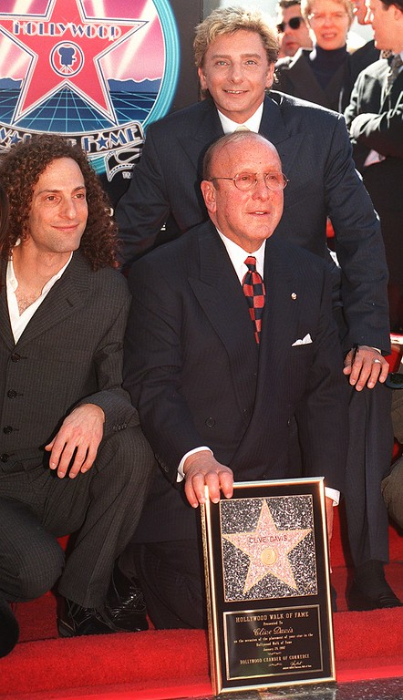 . Clive Davis, president of Arista Records, poses with Arista artists Kenny G, left, and Barry Manilow, background,  as he receives a star on the Hollywood Walk of Fame Tuesday, Jan. 28, 1997. Davis is the first active record company president to receive the honor. (AP Photo/Chris Pizzello)