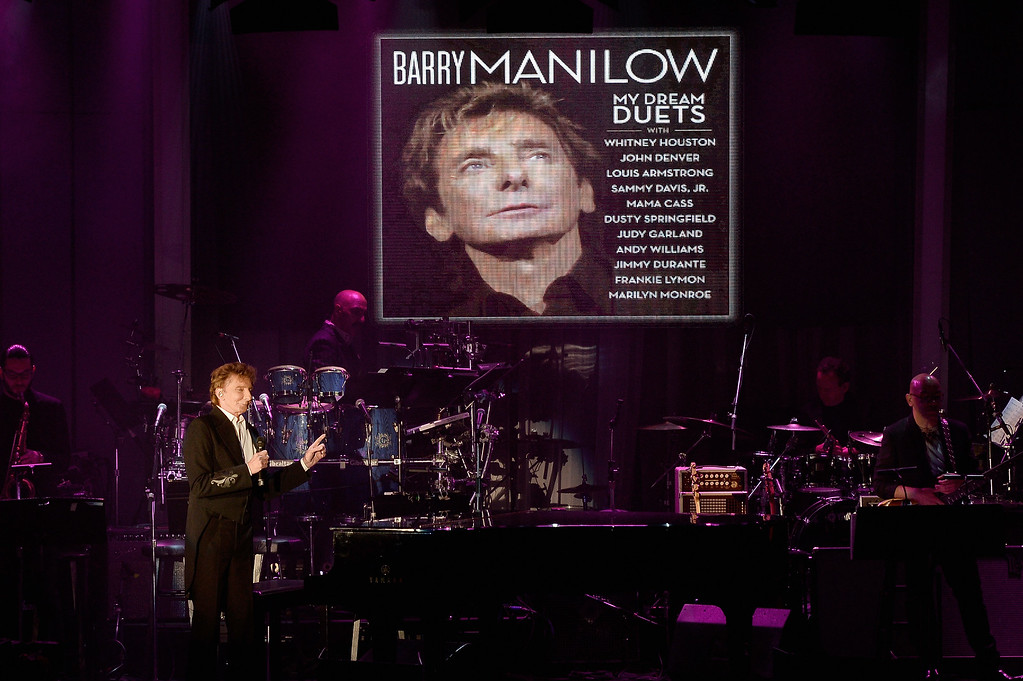 . BEVERLY HILLS, CA - FEBRUARY 14:  Recording artist Barry Manilow performs onstage as the image for his album \'My Dream Duets\' is displayed on a video screen during the 2016 Pre-GRAMMY Gala and Salute to Industry Icons honoring Irving Azoff at The Beverly Hilton Hotel on February 14, 2016 in Beverly Hills, California.  (Photo by Kevork Djansezian/Getty Images)