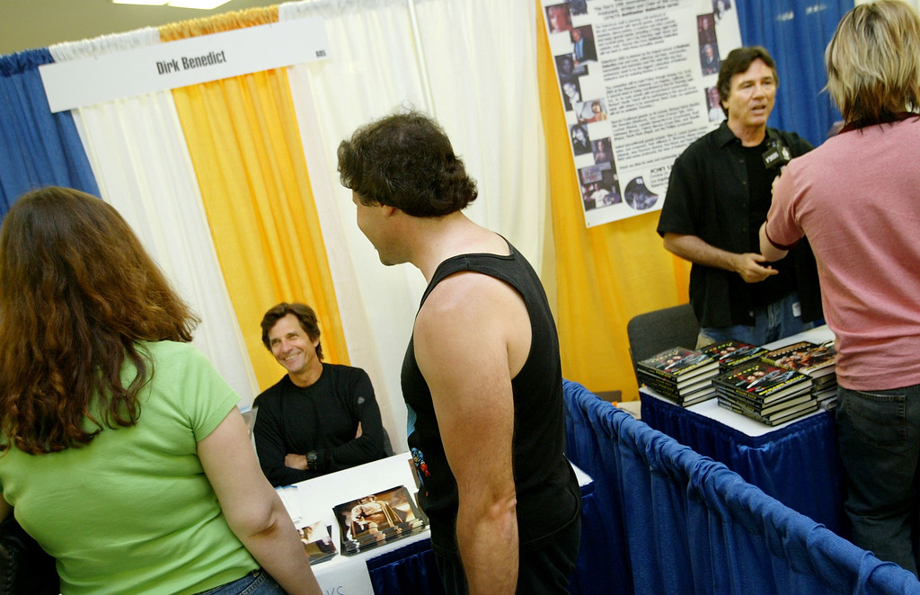 . Actors Dirk Benedict (L) and Richard Hatch (R) of the \'Battlestar Galactica\' television series, talk to fans at the Sci-Fi and Fantasy Creators Convention June 27, 2003 in New York City. The convention features hundreds of booths of science fiction-themed memorbilia. (Photo by Chris Hondros/Getty Images)