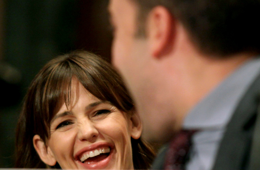 . Actress Jennifer Garner laughs with her husband, actor Ben Affleck, on Capitol Hill in Washington, Thursday, March 26, 2015, as Affleck testified before the Senate State, Foreign Operations, and Related Programs subcommittee hearing on diplomacy, development and national security. (AP Photo/Lauren Victoria Burke)