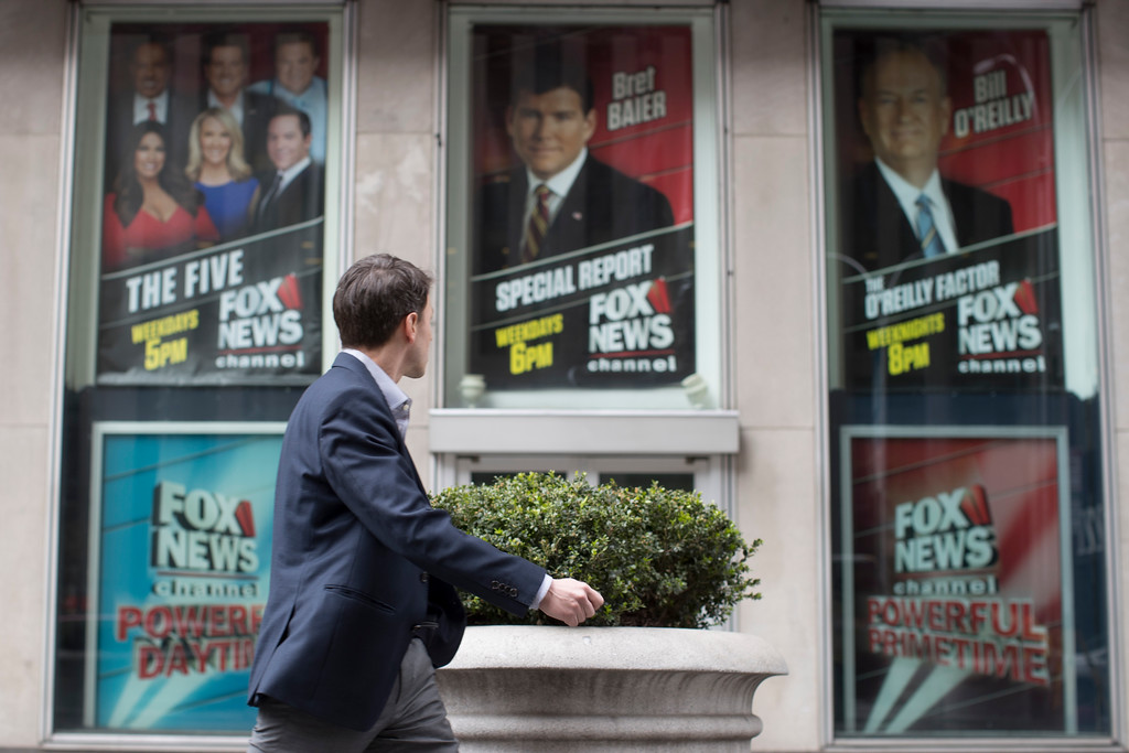 . A pedestrian walks past the News Corp. headquarters building in New York displaying posters featuring Fox News Channel personalities including Bill O\'Reilly, right, on Wednesday, April 19, 2017. O�Reilly will not be returning to the Fox News Channel, 21st Century Fox said in a statement on Wednesday, April 19, 2017. (AP Photo/Mary Altaffer)