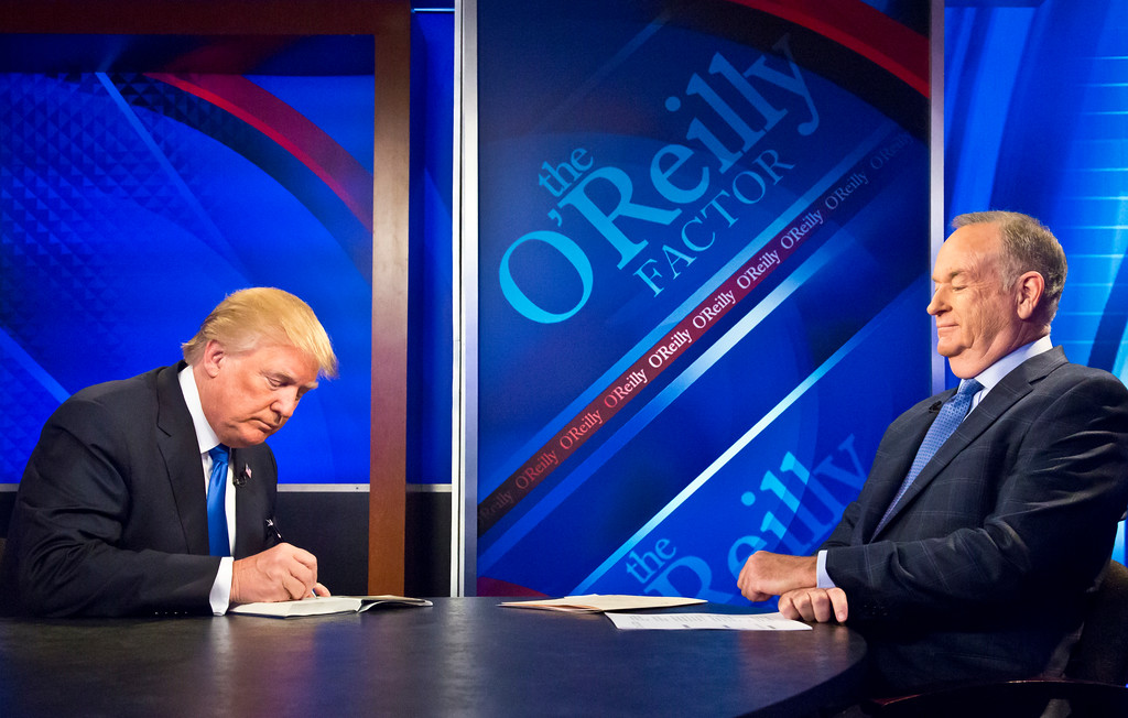 """. Republican presidential candidate Donald Trump, left, signs his book for Bill O\'Reilly, right, during his appearance on Fox\'s news talk show \""""The O\'Reilly Factor,\"""" Friday, Nov. 6, 2015, in New York.  The interview will air tonight on Fox News Channel�s The O�Reilly Factor.  (AP Photo/Bebeto Matthews)"""