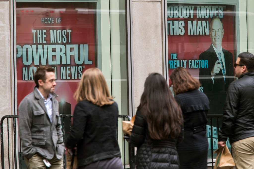 ". People walk past posters featuring Bill O\'Reilly as they enter the News Corp. headquarters in New York, Wednesday, April 19, 2017. O\'Reilly has lost his job at Fox News Channel following reports that five women had been paid millions of dollars to keep quiet about harassment allegations. 21st Century Fox issued a statement Wednesday that ""after a thorough and careful review of the allegations, the company and Bill O\'Reilly have agreed that Bill O\'Reilly will not be returning to the Fox News Channel.  (AP Photo/Mary Altaffer)"