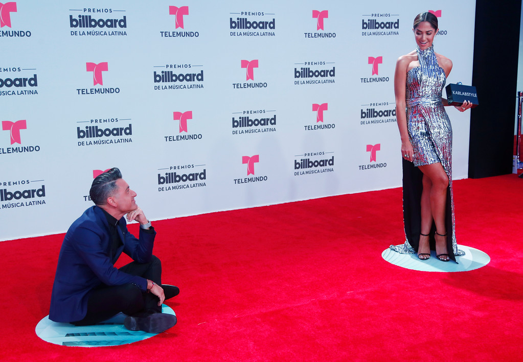 . TV personality Jorge Bernal watches his wife celebrity stylist Karla Birbragher, as they pose on the red carpet at the Latin Billboard Awards, Thursday, April 27, 2017 in Coral Gables, Fla. (AP Photo/Wilfredo Lee).