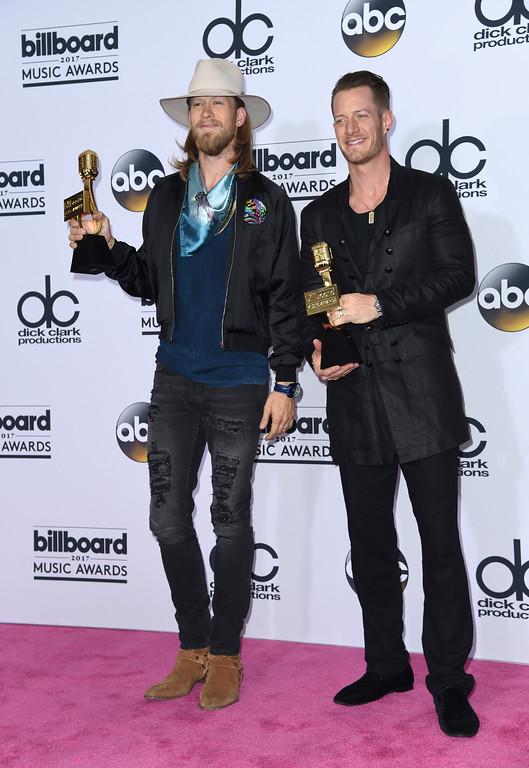 ". Brian Kelley, left, and Tyler Hubbard, of Florida Georgia Line, pose in the press room with their award for top country song for ""H.O.L.Y.\"" at the Billboard Music Awards at the T-Mobile Arena on Sunday, May 21, 2017, in Las Vegas. (Photo by Richard Shotwell/Invision/AP)"
