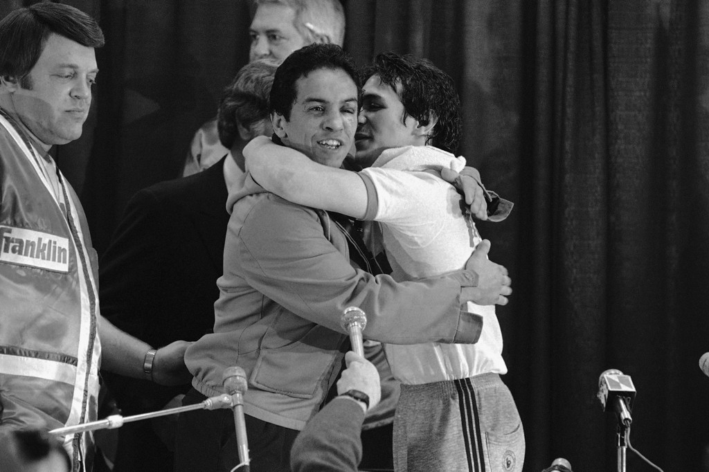 . WBA lightweight champ Ray Mancini, right, gives challenger Bobby Chacon a hug after defeating him in a title fight at Reno, Nov. 14, 1984. (AP Photo)