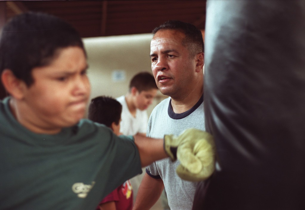 . 2001 file photo: A youngster works the heavy bag under the guidance of former boxing champion Bobby Chacon at Hillside Bible Baptist Church in Pacoima, California. (Hans Gutknecht/Los Angeles Daily News)
