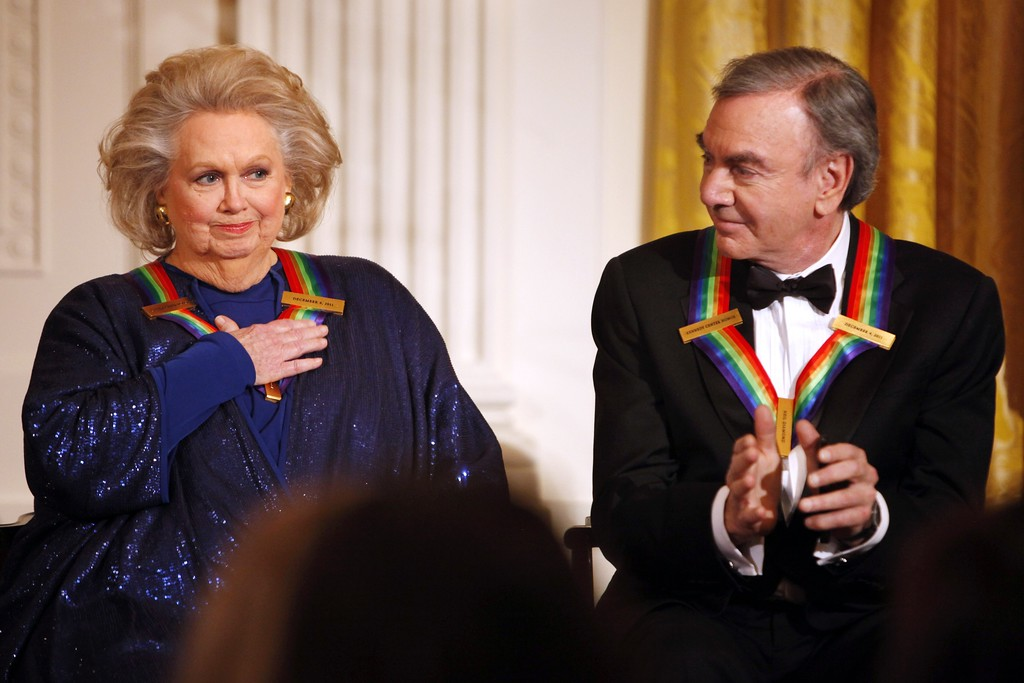 . FILE - In this Dec. 4, 2011 file photo, actress-singer Barbara Cook, left, reacts to remarks from President Barack Obama, next to fellow 2011 Kennedy Center Honors recipient singer and songwriter Neil Diamond, during at a reception for the honorees in the East Room of the White House, in Washington. Cook, whose shimmering soprano made her one of Broadway\'s leading ingenues and later a major cabaret and concert interpreter of popular American song, has died. She was 89. (AP Photo/Jacquelyn Martin, File)