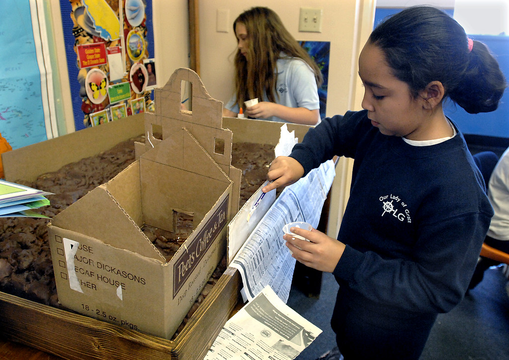 . Students Victoria Silva, left, and Samantha Ochoa paint the walls on  a model of a California mission being built by fourth-graders as a class project at Our Lady of Grace School in Encino on January 20, 2009. (Los Angeles Daily News file photo)
