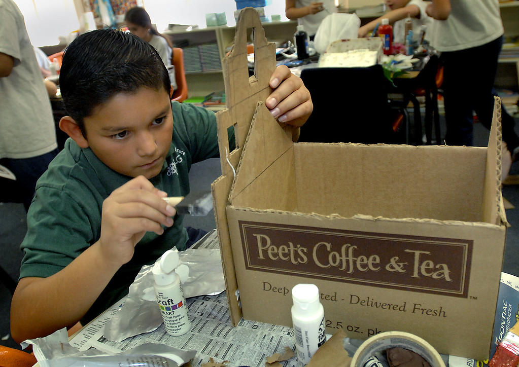. Student Joseph Silva paints the cardboard church for a model of a California mission being built by fourth-graders as a class project at Our Lady of Grace School in Encino on January 20, 2009. (Los Angeles Daily News file photo)