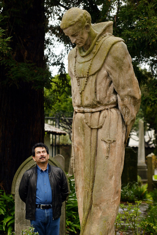 . Andrew Galvan, the first American Indian curator of Mission Dolores, or Mission San Francisco de Asís looks over a statue of Father Junipero Serra, in the cemetary of the historic church in San Francisco, Feb. 17, 2004. (AP Photo/Eric Risberg)
