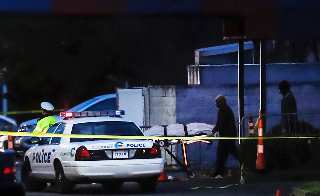 . A body is removed as police work at the Cameo club after a fatal shooting, Sunday, March 26, 2017, in Cincinnati. (AP Photo/John Minchillo)