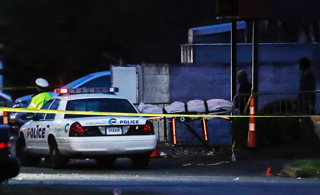. A body is removed as police operate at a crime scene outside the Cameo club after a fatal shooting, Sunday, March 26, 2017, in Cincinnati. (AP Photo/John Minchillo)