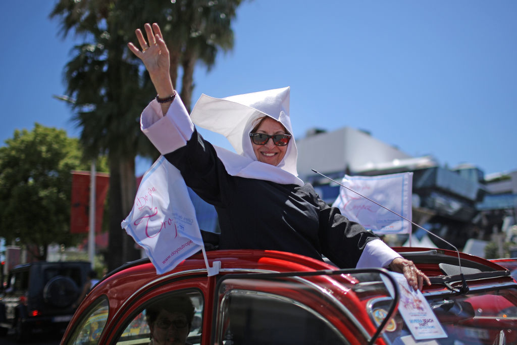 . CANNES, FRANCE - MAY 19:  A woman dressed as a nun promotes a beach party as they drive along the Boulevard de la Croisette during the Cannes Film Festival on May 19, 2017 in Cannes, France. Celebrities, fans and the movie world have descended on Cannes for this year\'s festival of the screen. For seventy years The Croisette Boulevard has always been the centre of athe place watch the rich and dandy and people from all walks of life to promenade.  (Photo by Christopher Furlong/Getty Images)