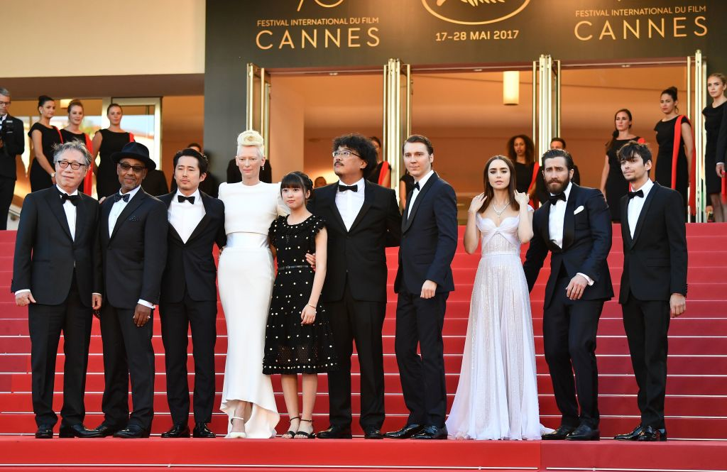 . (From R) Canadian actor Devon Bostick, US actor Jake Gyllenhaal, British actress Lily Collins, US actor Paul Dano, South Korean director Bong Joon-ho, South Korean actress Ahn Seo-hyun, British actress Tilda Swinton, US-South Korean actor Steven Yeun, Danish-born actor Giancarlo Esposito and South Korean actor Byung Hee-bong pose as they arrive on May 19, 2017 for the screening of the film \'Okja\' at the 70th edition of the Cannes Film Festival in Cannes, southern France.  (ALBERTO PIZZOLI/AFP/Getty Images)