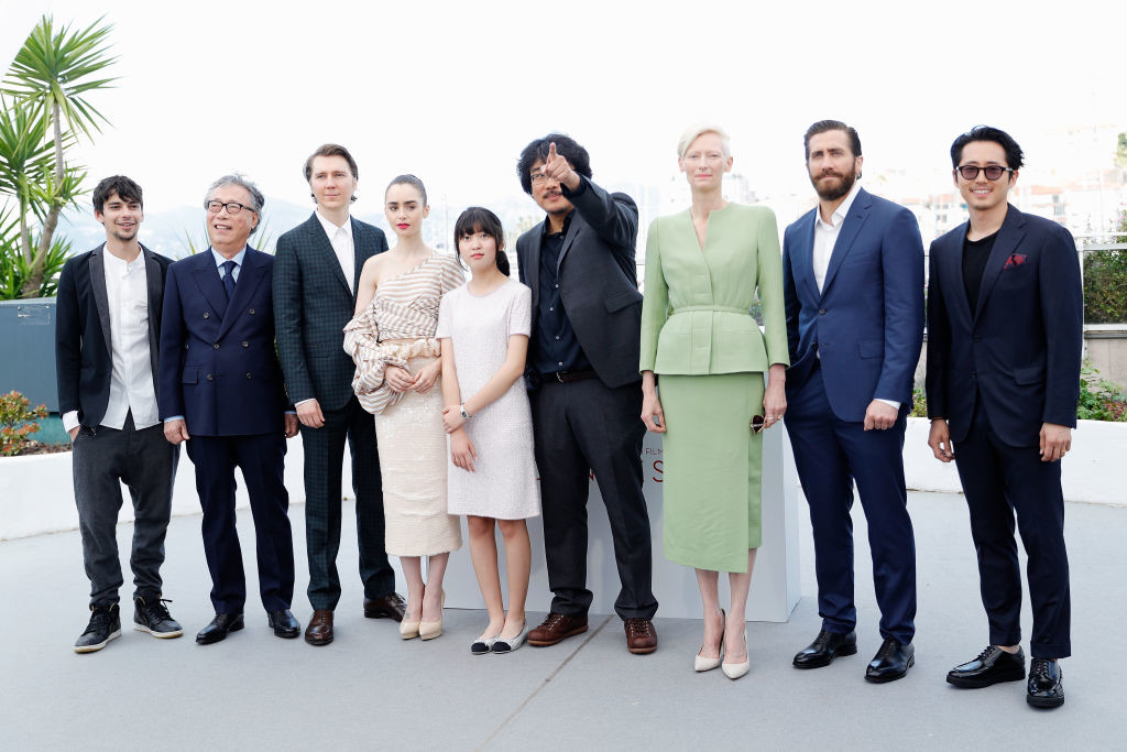 ". CANNES, FRANCE - MAY 19:  (L-R) Actors Devon Bostick, Byung Heebong, Paul Dano, Lily Collins, director Bong Joon-Ho, actors Tilda Swinton, Jake Gyllenhaal and Steven Yeun attend the ""Okja\"" photocall during the 70th annual Cannes Film Festival at Palais des Festivals on May 19, 2017 in Cannes, France.  (Photo by Andreas Rentz/Getty Images)"