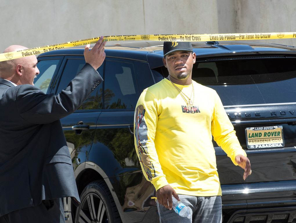 . An officer lifts the police tape as man leaves entertainer Chris Brown\'s home at the 5000 block Corbin Ave in Tarzana CA on Tuesday, August 30, 2016. (Photo by ED CRISOSTOMO, STAFF PHOTOGRAPHER)