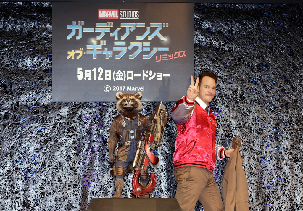". American actor Chris Pratt flashes a peace sign as he walks by a figure of a character ""Rocket Raccoon\"" after a media conference of \""Guardians of the Galaxy Vol. 2\"" in Tokyo, Tuesday, April 11, 2017. (AP Photo/Eugene Hoshiko)"