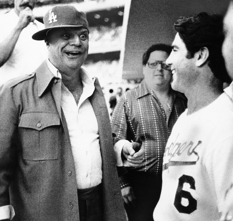 . Comedian Don Rickles tries on the cap of Los Angeles Dodgers Steve Garvey, right, while visiting in the dugout before the start of the second game in the National League playoffs on Wednesday, Oct. 5, 1977 in Los Angeles. (AP Photo)