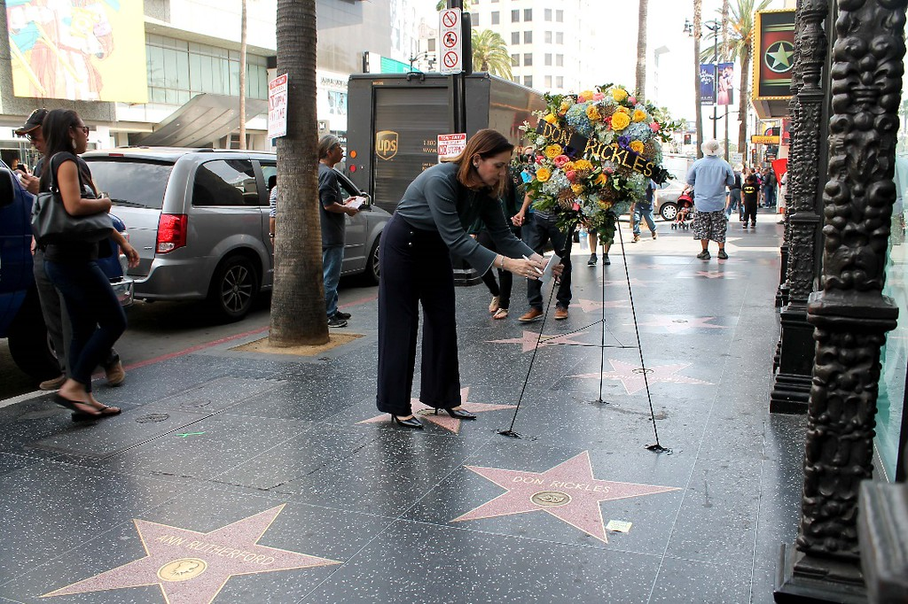 """. Ana Martinez, Producer of the Hollywood Walk of Fame, places flowers on the Hollywood Walk of Fame star of Don Rickles. Rickles, the hollering, bald-headed \""""Merchant of Venom� whose barrage of barbs upon the meek and the mighty endeared him to audiences and his peers for decades died, Thursday, April 6, 2017 at his home in Los Angeles. He was 90.   (Photo courtesy Hollywood Chamber of Commerce)"""