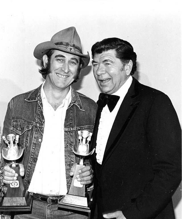 . Country singer Don Williams, left, poses with two awards presented to him by actor Claude Aiken for the single record of the year, during the 14th annual Country Music Awards in Los Angeles, Calif., on May 3, 1979. (AP Photo)
