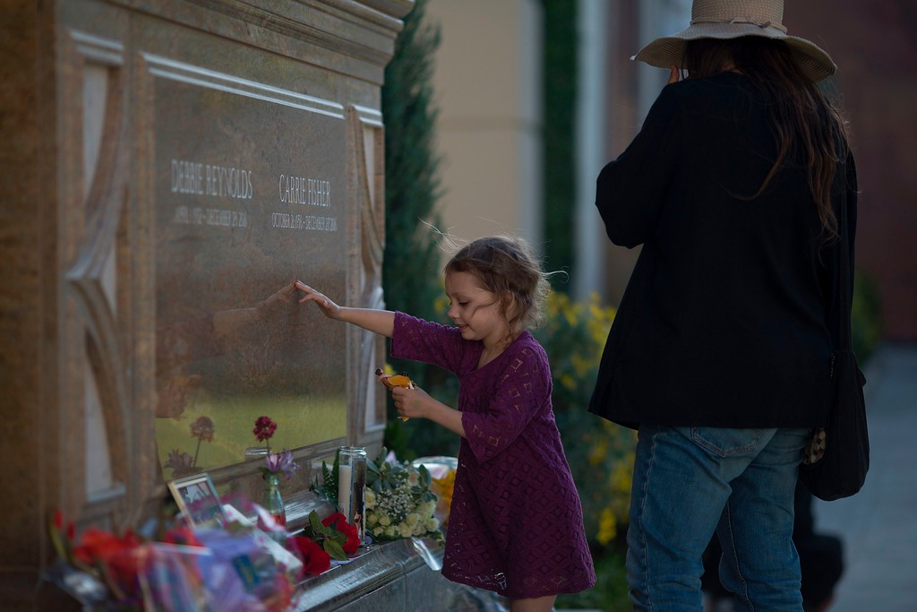 . People visit the joint gravesite for Carrie Fisher and her mother Debbie Reynolds following a public memorial on March 25, 2017 in Los Angeles, California.  Friends, family and hundreds of wellwishers gathered to celebrate the lives of beloved celebrity mother and daughter Debbie Reynolds and Carrie Fisher who died within a day of each other in late December 2016. (DAVID MCNEW/AFP/Getty Images)