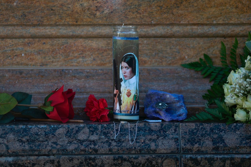 . A candle of Carrie Fisher as Princess Leia Organa stands graveside following a public memorial for Carrie Fisher and her mother Debbie Reynolds on March 25, 2017 in Los Angeles, California.  Friends, family and hundreds of wellwishers gathered to celebrate the lives of beloved celebrity mother and daughter Debbie Reynolds and Carrie Fisher who died within a day of each other in late December 2016. (DAVID MCNEW/AFP/Getty Images)