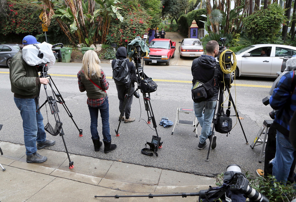 . Journalists stand outside the homes of Debbie Reynolds and Carrie Fisher in Los Angeles on Thursday, Jan. 5, 2017. A procession of stars arrived at the next door homes of Reynolds and her daughter Fisher on a gloomy Thursday afternoon amid reports that a private memorial was scheduled at the compound to mourn the late actresses. (AP Photo/Reed Saxon)