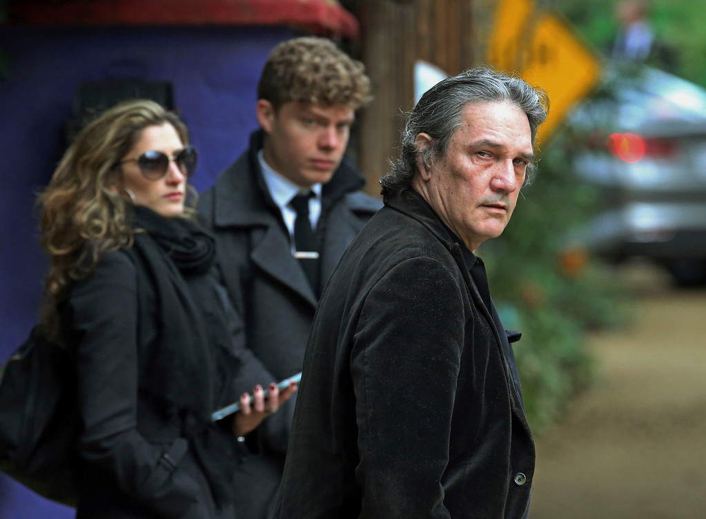 . A man, center checks guests in as they arrive for a memorial service at the homes of Debbie Reynolds and Carrie Fisher in Los Angeles on Thursday, Jan. 5, 2017. A procession of stars arrived at the next door homes of Reynolds and her daughter Fisher on a gloomy Thursday afternoon amid reports that the private memorial was scheduled at the compound to mourn the late actresses. (AP Photo/Reed Saxon)