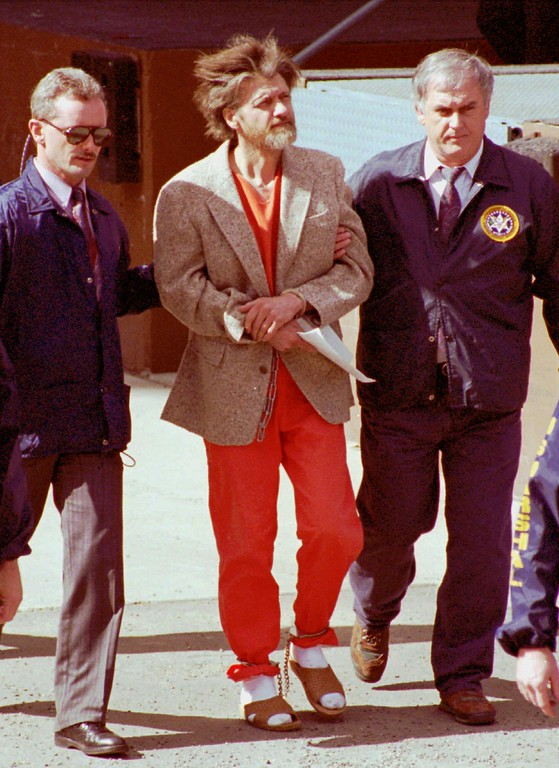 . File - Wearing a sport coat over his jail coveralls, Theodore John Kaczynski is escorted in handcuffs and ankle shackles by two unidentified federal agents as they leave the federal courthouse in Helena, Mont., Thursday, April 4, 1996.  Federal agents found a partially assembled bomb in the mountain shack of the former Berkeley math professor suspected of being the Unabomber.  (AP Photo/John Youngbear)