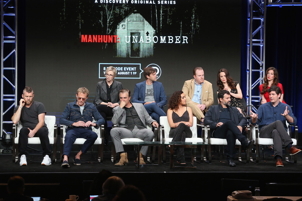 . BEVERLY HILLS, CA - JULY 26:  (L-R Front Row) Sam Worthington, Paul Bettany, Chris Noth, Keisha Castle-Hughes, showrunner/executive producer/director Greg Yaitanes, writer/executive producer Andrew Sodroski, (L-R Back Row) Jane Lynch, Mark Duplass, Jeremy Bobb, Elizabth Reaser and Lynn Collins of \'Discovery Channel - Manhunt: Unabomber\' speak onstage during the Discovery Communications portion of the 2017 Summer Television Critics Association Press Tour at The Beverly Hilton Hotel on July 26, 2017 in Beverly Hills, California.  (Photo by Frederick M. Brown/Getty Images)